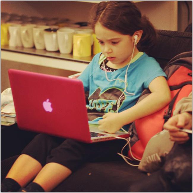 Niña pequeña sentada jugando en un MacBook rosado y usando audifonos.