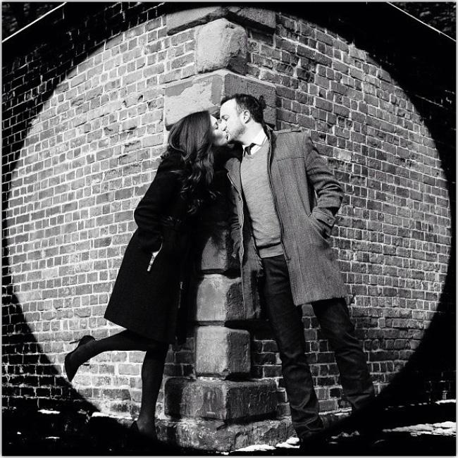 Foto en blanco y negro de pareja besandose en la esquina de una calle, apoyados sobre la pared.