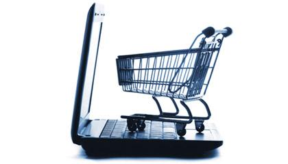 Carro de compras de supermercado sobre el teclado de un laptop