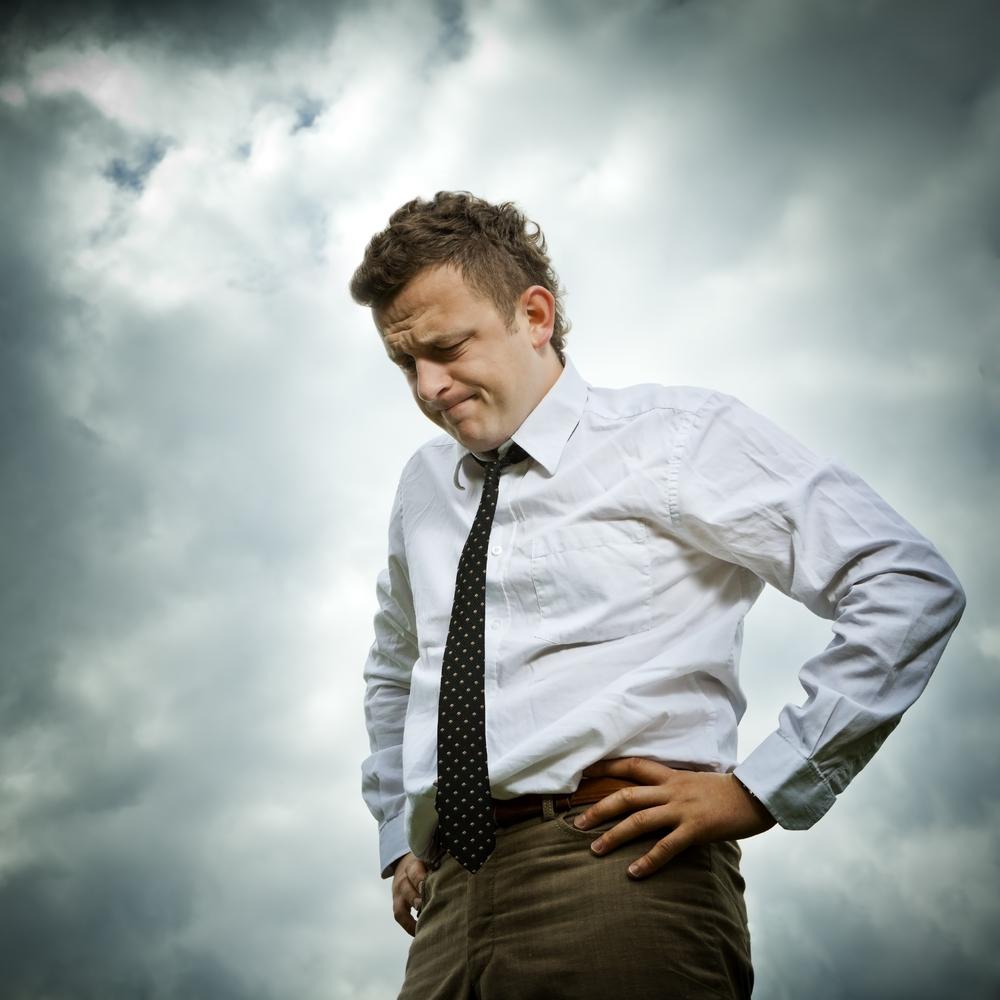 Hombre vestido con corbata con rostro de frustración y mirando hacia el suelo.