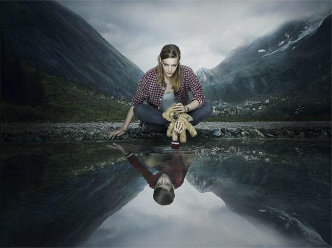 Mujer con oso de felpa sentada al borde de un lago donde se ve reflejada su imagen de niña