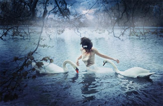 Mujer en un lago bailando con dos cisnes