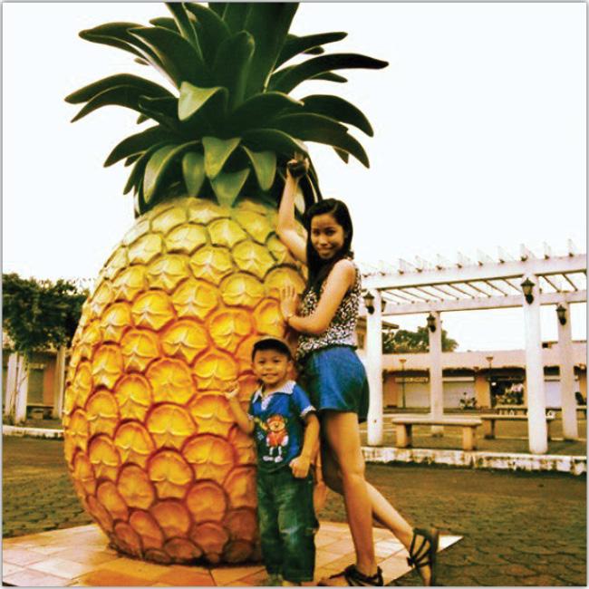 Piña gigante con dos niños abrazándola