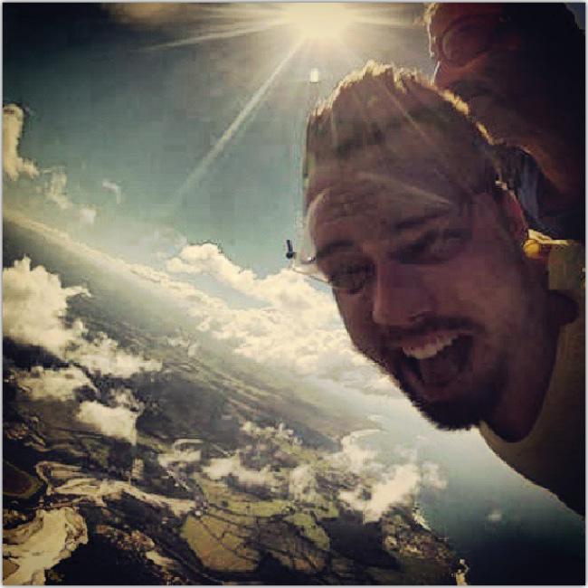 Imagen del rostro de un hombre saltando de un avión en paracaidas.