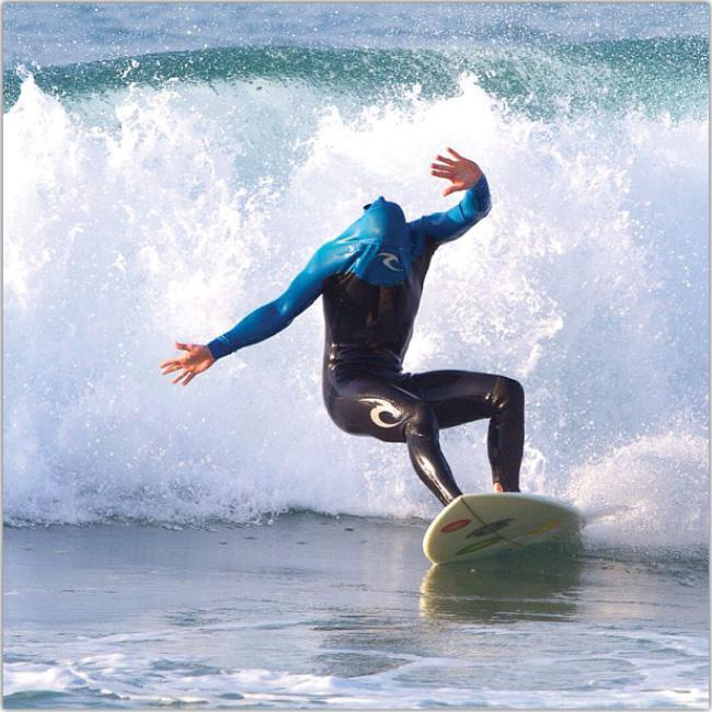 Hombre surfeando con el traje cubriéndole la cabeza.