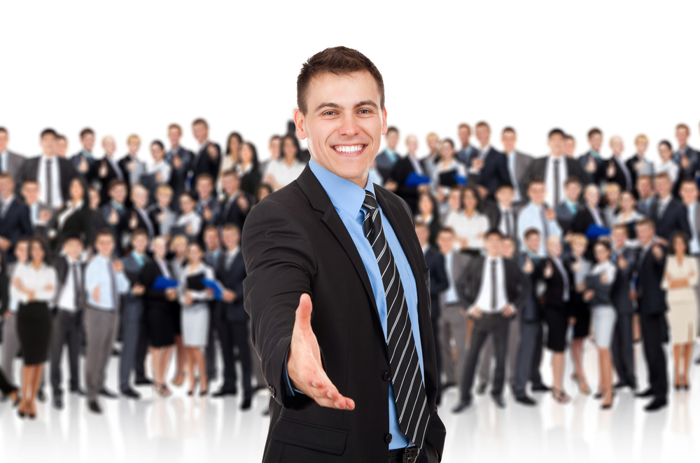 Ejecutivo con un enorme equipo de profesionales detrás de el, estirando la mano y dando la bienvenida.
