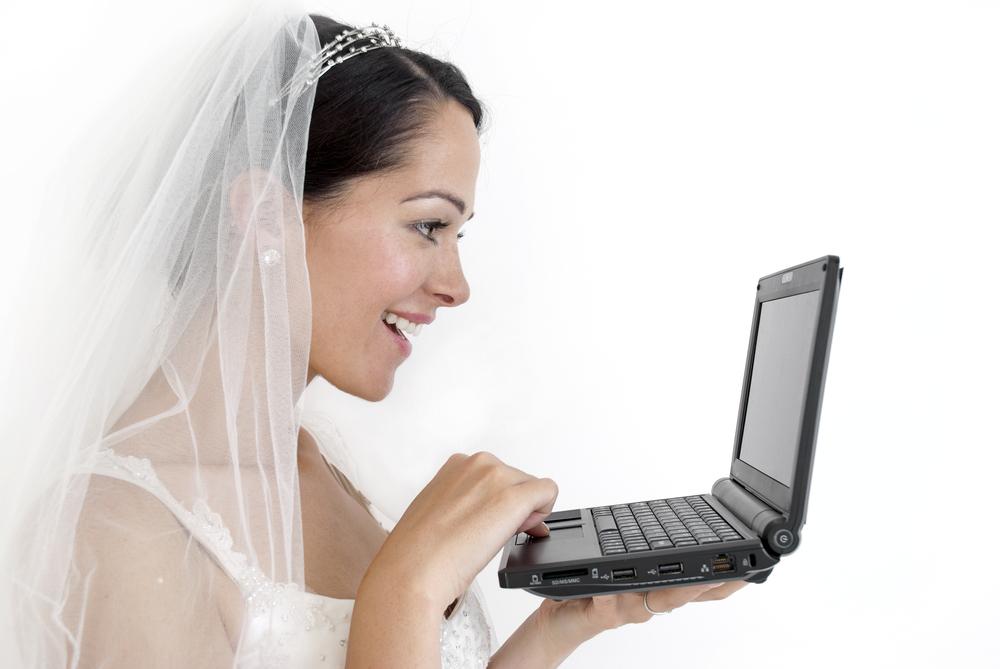 Novia con traje de novia frente a su laptop
