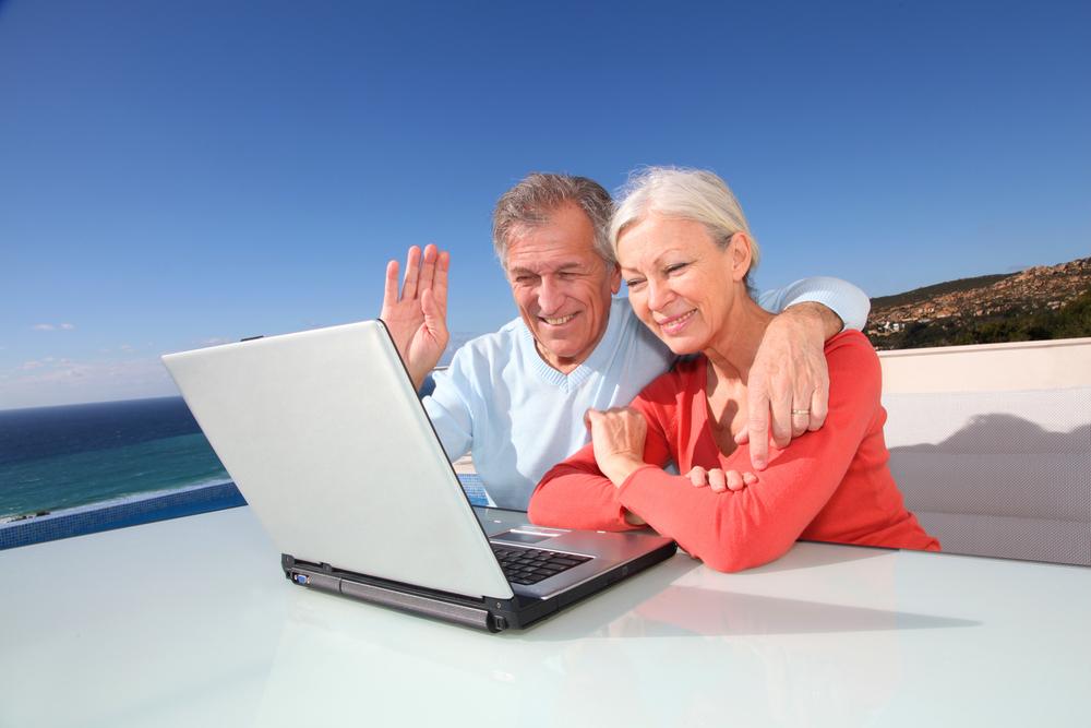 Un matrimonio mayor mira la pantalla de un computador y saludan amablamente hacia la cámara de la misma.