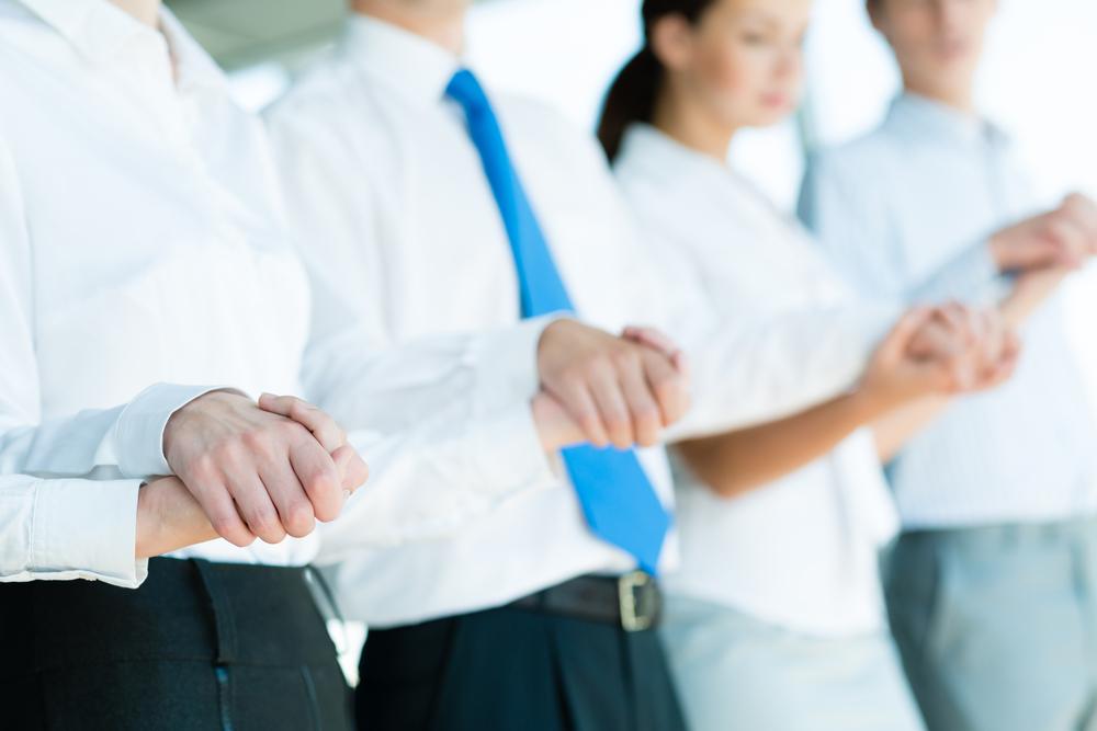 Muchos oficinistas/ejecutivos en primer plano tomados de las manos.