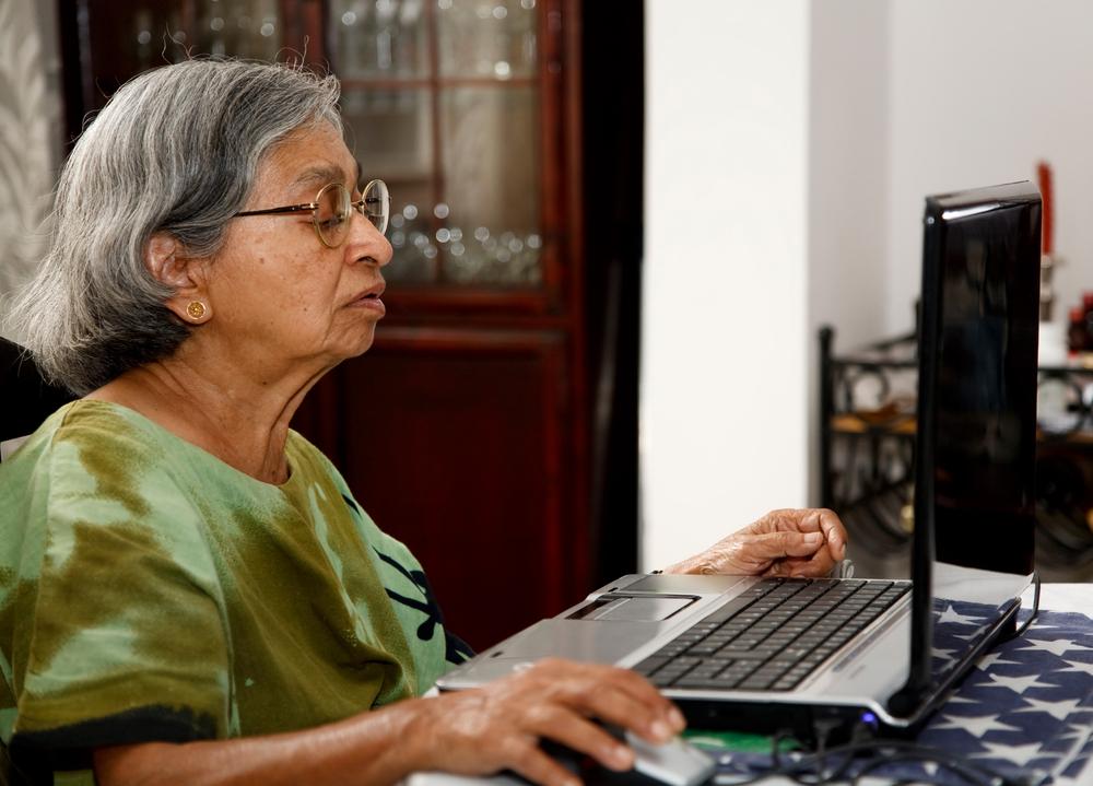 Mujer de edad avanzada sentada frente a un laptop