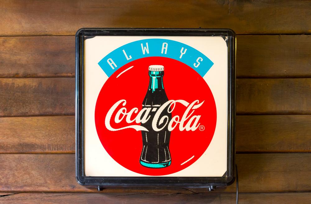 Anuncio de Coca Cola en una pared de madera