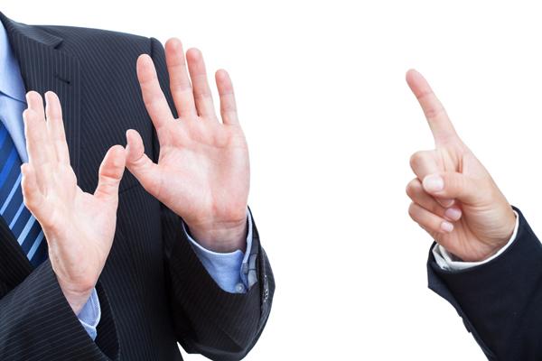 Dos ejecutivos vistos de cerca. Uno apunta con el dedo y el otro hace una seña con ambas palmas enfrentandolo.