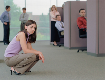 Grupo de oficinistas se asomand esde dentro de sus cubículos y una de ellos se sienta en el pasillo