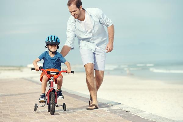 Hombre corriendo por la playa mientras le enseña a su hijo pequeño a andar en bicicleta