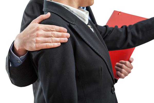 Un ejecutivo sostiene una carpeta roja y con la otra mano, abraza a una ejecutiva.
