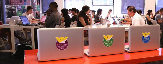 Tres computadores laptop juntos y abiertos con el logo de Wix sobre ellos