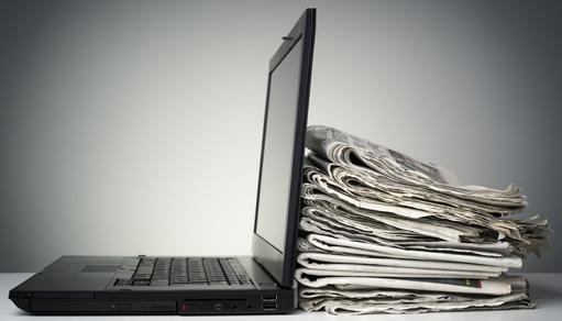 Notebook con una pila de periodicos detrás de el
