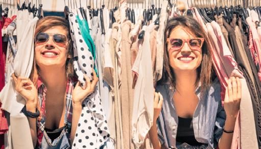 Dos jóvenes asoman de entre un montón de ropa