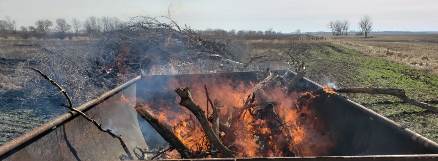 Waste wood burns in oil tank repurposed as a kiln.