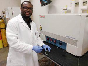 Man in lab coat prepares to load sample into lab equipment.