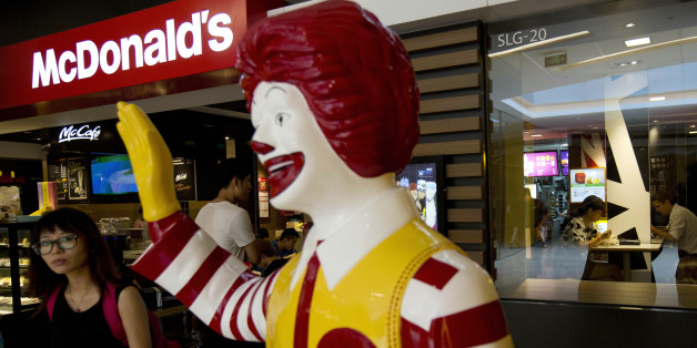 FILE - In this Thursday, July 31, 2014 file photo, a customer walks past a statue of Ronald McDonald on display outside a McDonald's restaurant in Beijing. McDonald's Corp. on Monday, Nov. 10, 2014 said that a key global sales figure slipped 0.5 percent in October, with weakness in the U.S. and ongoing difficulties from a food-safety scandal in China weighing down its business. (AP Photo/Andy Wong, File)