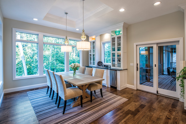 two hand crafted light fixtures with specialty blown glass hang above the dining room table and gorgeous built in millwork completes the rooms wet bar - 2 Pendant Lights Over Dining Table