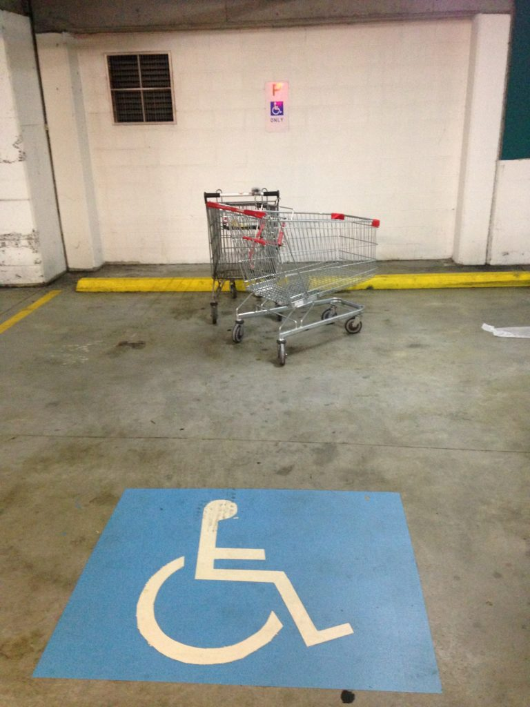 Another shopping trolley in an accessible parking bay.
