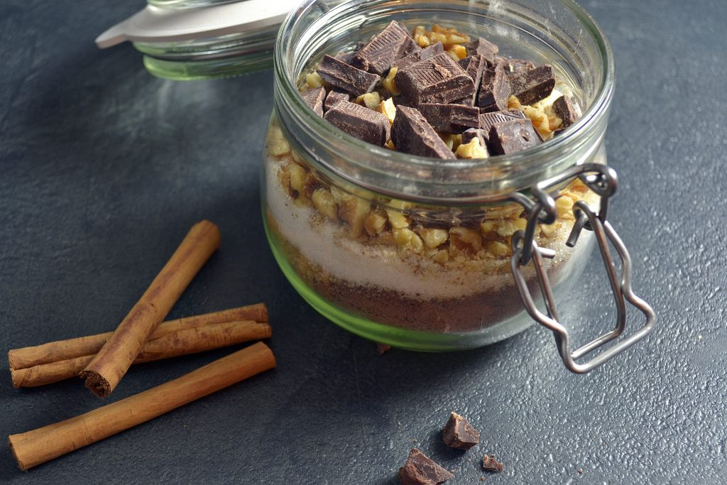 cinnamon sticks next to a small jar filled with walnuts, chocolate, and baking goods.