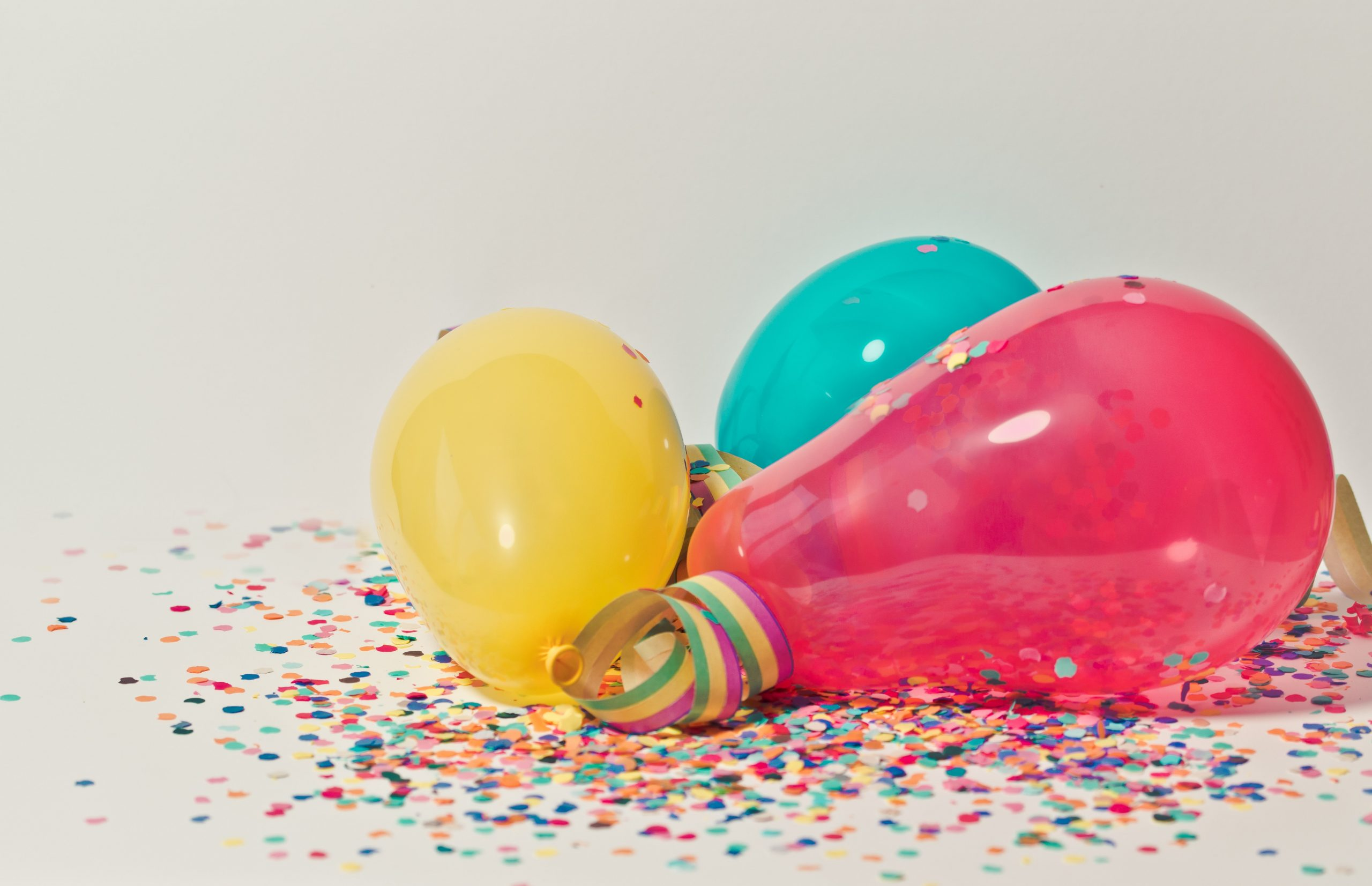 yellow, teal, and hot pink balloons rest on confetti and streamers