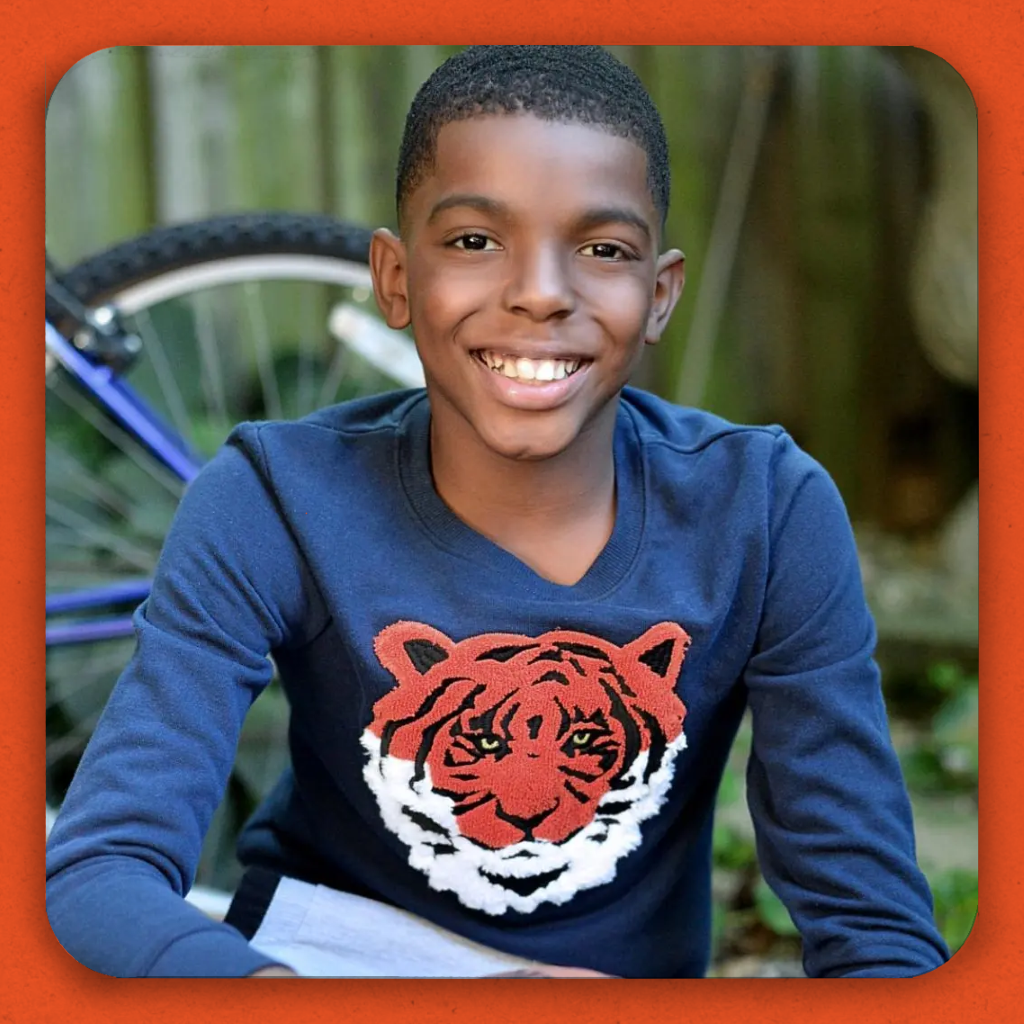 A smiling black boy in a tiger shirt