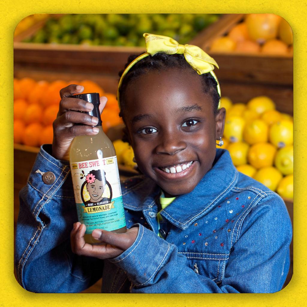 A grinning black girl holding a bottle of her lemonade