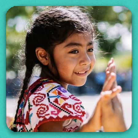 A smiling latina girl holding someone's hand.