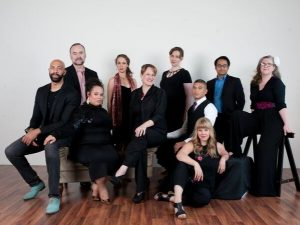 people in black clothes pose for a group photograph