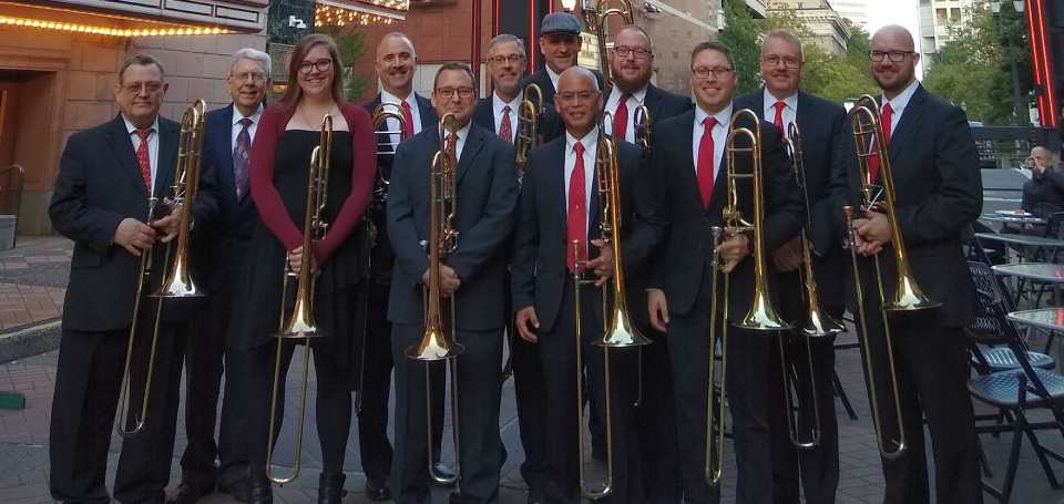 Rose City Trombones group standing in front of a concert hall