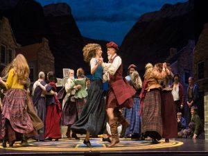 Man and woman dancing in Scottish garb