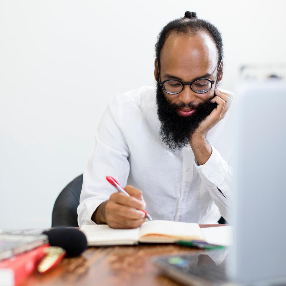 man sitting at desk in white shirt