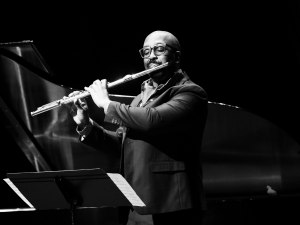 man playing flute on stage in black and white