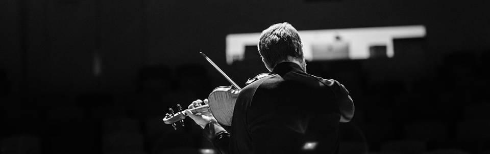 Image from behind of Tomas Cotik playing violin