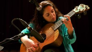 Milagro Theatre image; woman with guitar