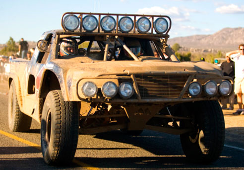 Red Bull Trophy Truck running the Baja 1000 covered in mud, seen from the front