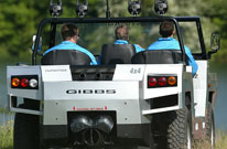 Humdinga amphibious all terrain vehicle seen from the rear as it drives on dirt