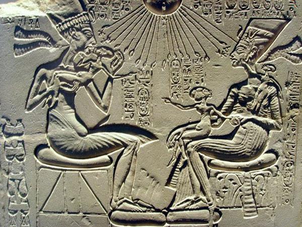 Imagen de un petroglifo egipcio en donde dos deidades faraónicas tienen en brazos e bebes con fisonomía extraterrestre.
