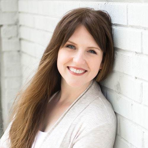image is of Rev. Laura C. Cannon smiling into the camera, leaning against a white brick wall, she is wearing a white sweater and has long brown hair past her shoulders