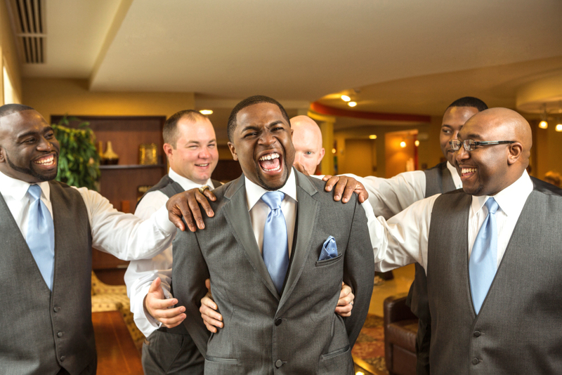 a group of men dressed up in wedding attire, gray suit vests with button up shirts and ties, laughing and reaching out toward the groom, who is also laughing