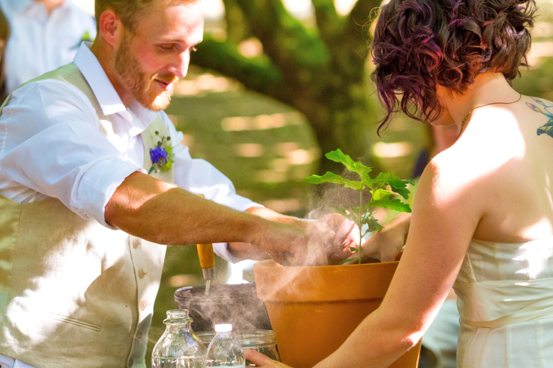 Image of a young couple planting a green leafy plant as part of a unity ceremony together in a pot outside in the sunlight, the man is smiling and wearing a dress shirt and vest with wedding flowers and the woman is wearing a white wedding dress.