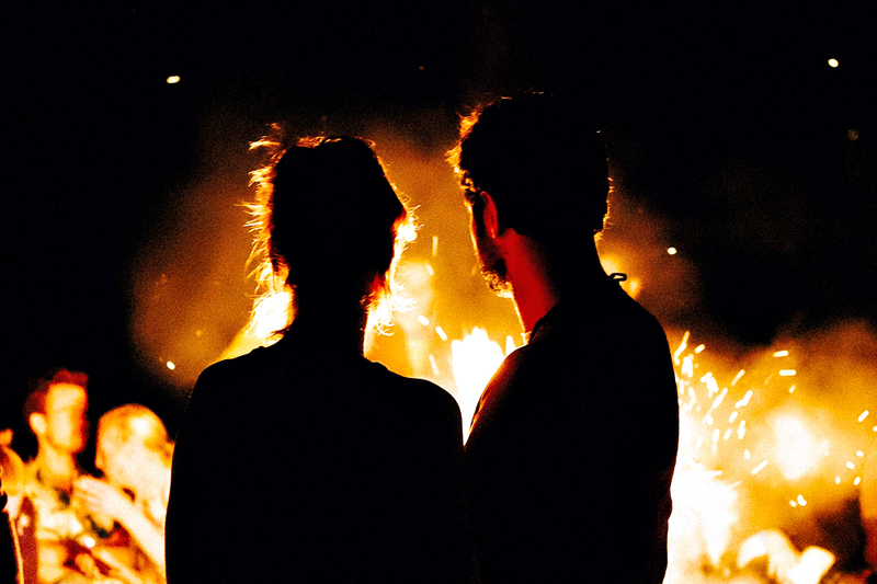 image is of a young couple, a man and woman, taken from behind as they stare into the glowing orange flames of a large beltane bonfire