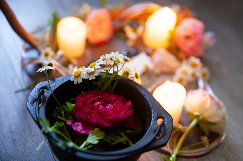 image is a photograph of a pagan wedding altar with a flower and candle and other beautiful objects