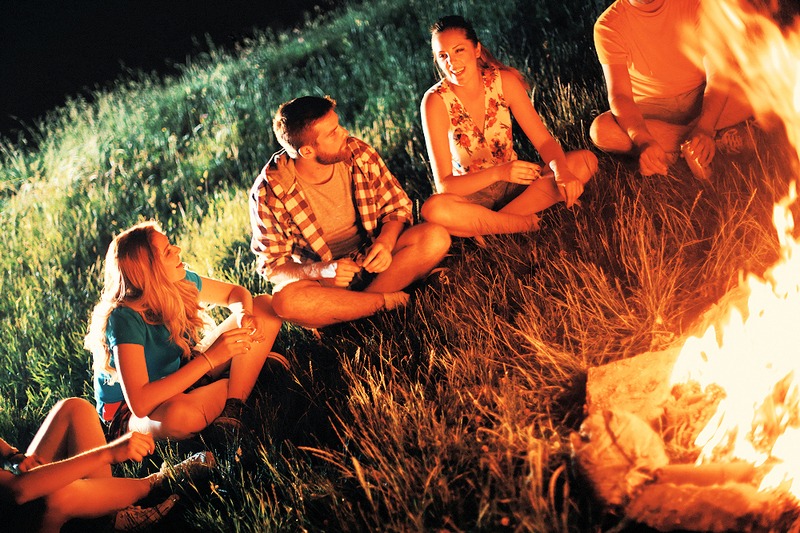 image is of a group of happy people sitting around a bonfire smiling as they celebrate Beltane