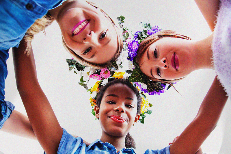 image is a photograph taken from below, looking up, at three smiling woman with floral wreaths on their heads in celebration of beltane
