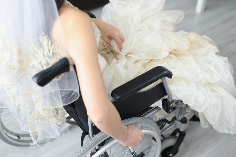 image is a photograph of a young woman in a wheelchair wearing a white wedding dress with veil